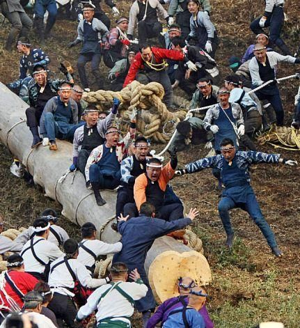 Onibashira, Japan, men riding a log down a hill