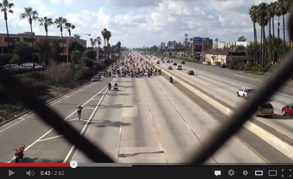 Hundreds of bikers approach the overpass at a California freeway for a proposal