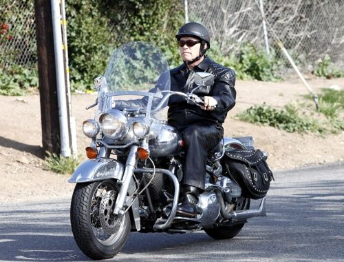 Arnold Schwarzenegger riding what looks like a Harley